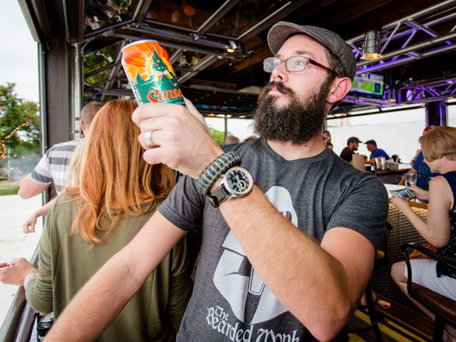 A man examines a can of Sunset Lager from Audacity Brewing Company, a local craft brewery in Denton.