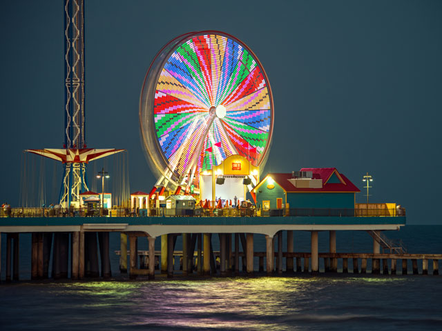 The shining neon lights of Galveston's Pleasure Pier illuminate the night sky.