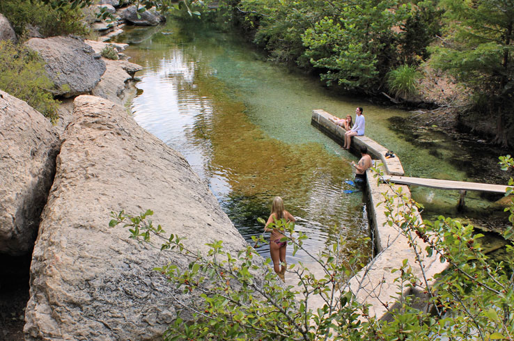 A girl prepares to dive into the crystal clear waters at Jacob's Well.