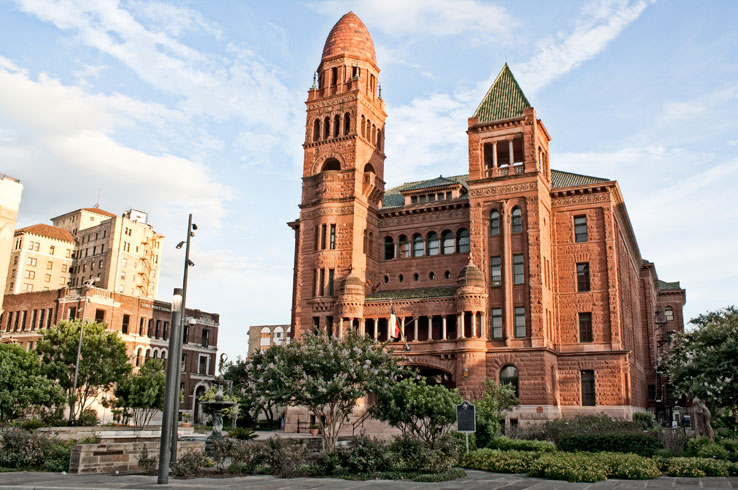 A setting sun casts an orange glow on the old Bexar County Courthouse, a Romanesque-style building made of red sandstone.